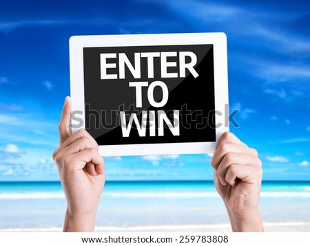 Tablet pc with text Enter to Win with beach background - stock photo