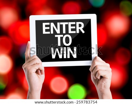 Tablet pc with text Enter to Win with bokeh background  - stock photo
