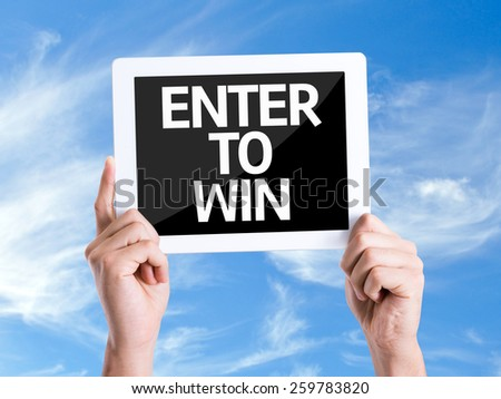 Tablet pc with text Enter to Win with sky background  - stock photo
