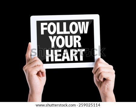 Tablet pc with text Follow Your Heart isolated on black background - stock photo