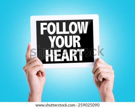 Tablet pc with text Follow Your Heart with blue background - stock photo