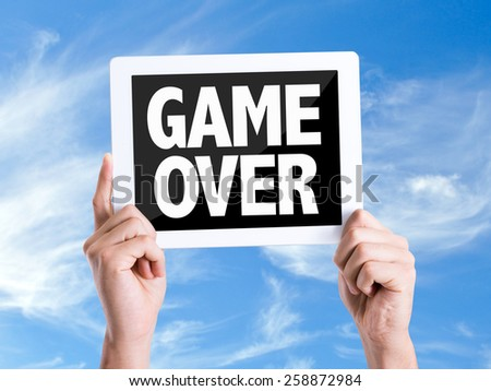 Tablet pc with text Game Over with sky background - stock photo