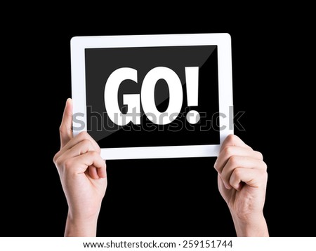 Tablet pc with text GO! isolated on black background - stock photo