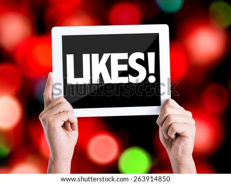 Tablet pc with text Likes with bokeh background - stock photo