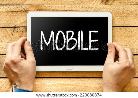 "Tablet PC with text ""Mobile"". Hands hold tablet PC with text ""Mobile"" over wooden table  - stock photo"