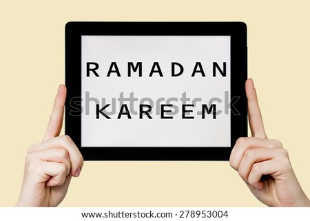 Tablet pc with text Ramadan kareem with yellow background - stock photo