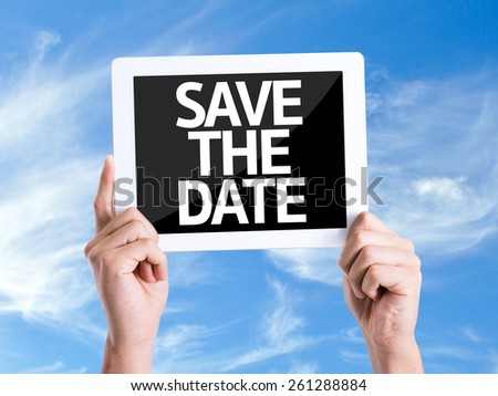 Tablet pc with text Save the Date with sky background - stock photo