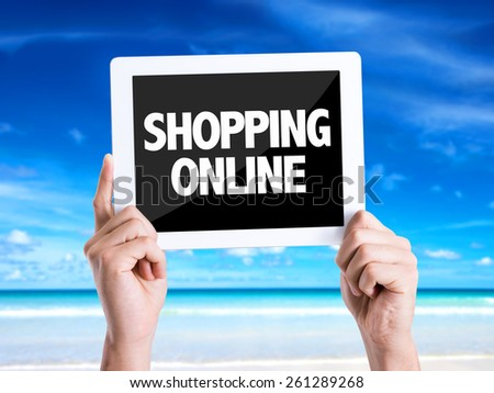 Tablet pc with text Shopping Online with beach background - stock photo