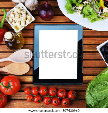 tablet , salad with feta cheese and fresh vegetables on wooden background - stock photo