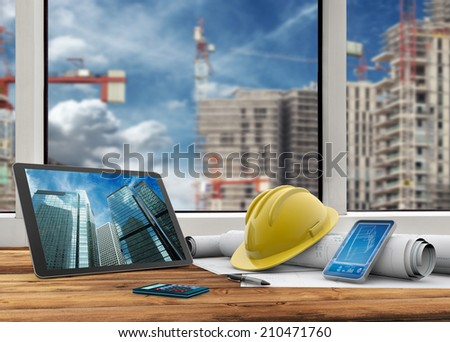 tablet, smart phone, safety helmet and blueprints in construction site - stock photo