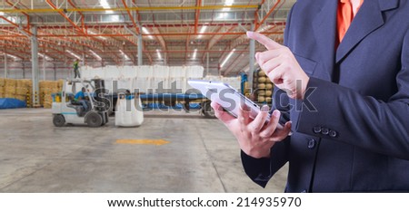 tablet to handle export and import goods prepare the delivery of powder bag in warehouse - stock photo