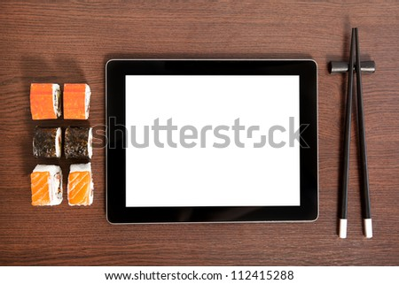 tablet touch computer gadget with isolated screen on a table near sushi - stock photo