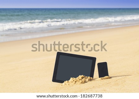 tablet touch pad computer and mobile in the sand on beach