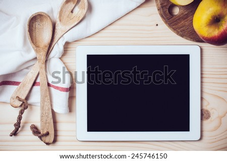 Tablet, towel and cooking utensils on wooden kitchen table, a blank screen. - stock photo