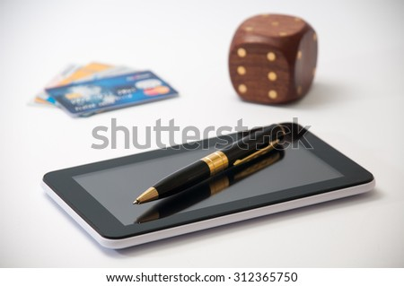 Tablet with a black pen, wooden dice and credit cards in the background. - stock photo