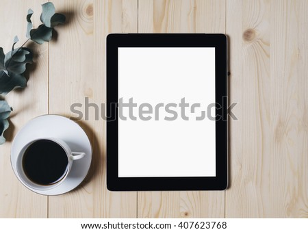 Tablet with a clean blank screen monitor with a branch of eucalyptus and a cup of coffee on a wooden background with natural wood planks top view horizontal, space for your information or content