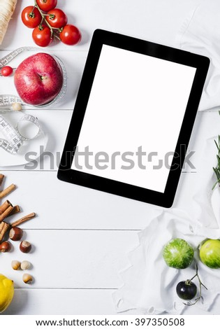 Tablet with a measuring tape, rosemary, lime, lemon, nuts, tomatoes, cinnamonnand red apples on a white wooden background top view vertical - stock photo