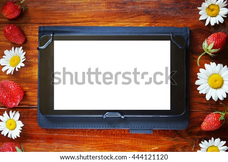Tablet with a white screen on the wooden background with fresh strawberries and chamomiles - stock photo