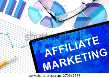 Tablet with affiliate marketing, graphs and glasses.  - stock photo