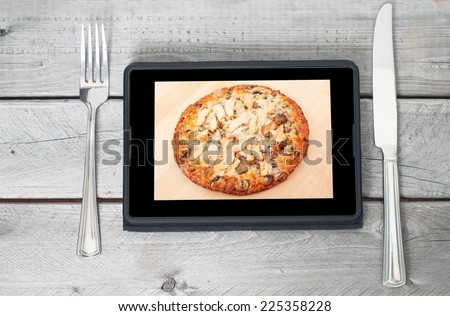 Tablet with an appetizing chicken pizza on its display between a fork and knife - stock photo