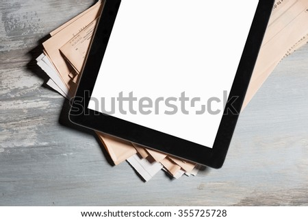Tablet with blank screen and newspapers  - stock photo