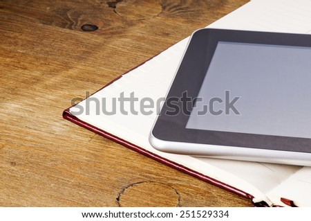 Tablet with blank screen and notebook with leather cover on wooden table - stock photo