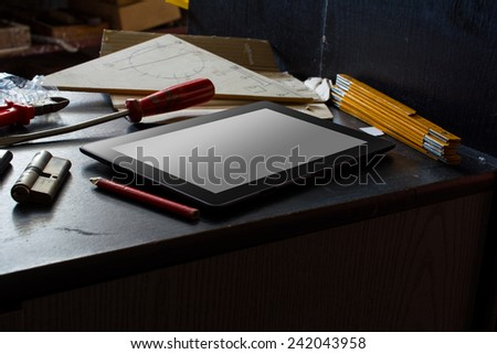 Tablet With Blank Screen On A Dark Cupboard With A Set Of Tools In A Dirty Basement