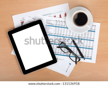 Tablet with blank screen over papers with numbers and charts, coffee cup, glasses and pen. View from above - stock photo