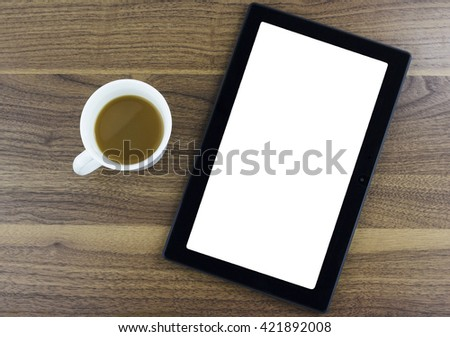 Tablet with blank screen sitting next to a cup of coffee