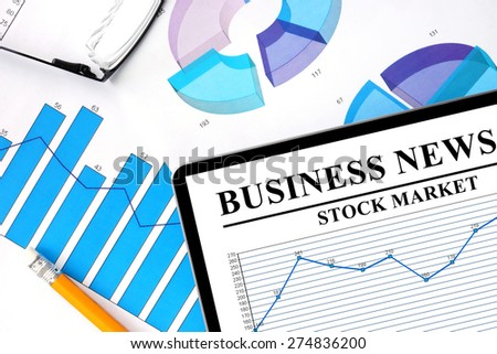 Tablet with  business news of stock market and graphs.  - stock photo