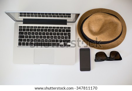 Tablet with clean screen on wooden table. Fashionable clothes sunglasses, hat, Flat mock up for design. Top view. - stock photo