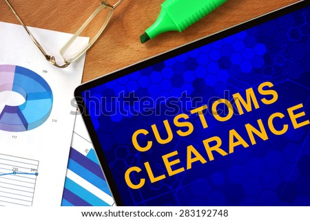 Tablet with Customs Clearance  and charts on a wooden board. - stock photo