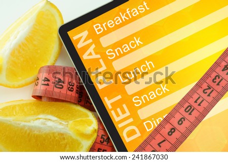 Tablet with diet plan and measuring tape on white background - stock photo