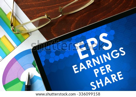 Tablet with earnings per share (EPS) on a table. Business concept. - stock photo