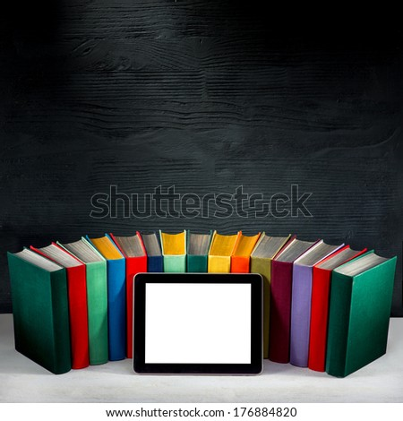 tablet with empty screen with colorful books on background with place for your text - stock photo