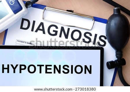 Tablet with  hypotension, form with word diagnosis and blood pressure meter  - stock photo