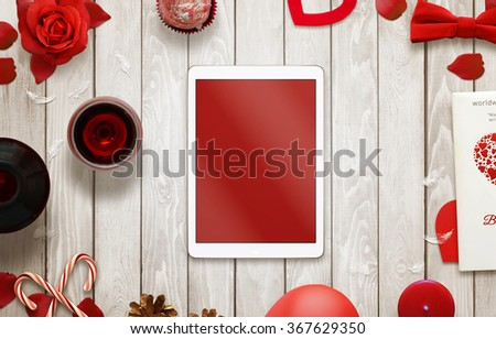 Tablet with isolated screen on wooden background. Love scene with hearts, gift, candle, petals, rose - stock photo