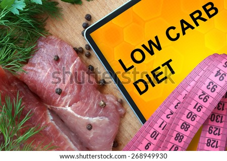 Tablet with low carb diet and fresh meat  on wooden board - stock photo