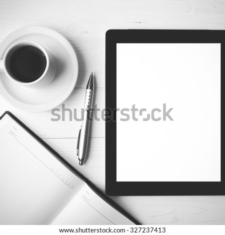 tablet with notebook and coffee cup over white table black and white color style