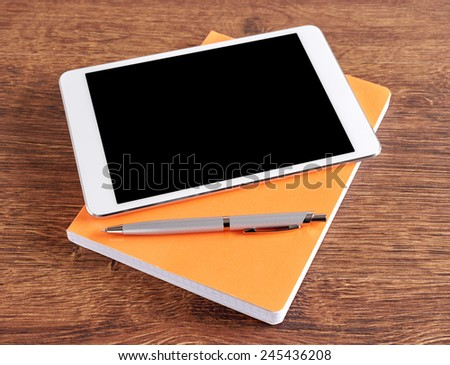 Tablet with notebook on wooden table and pen - stock photo