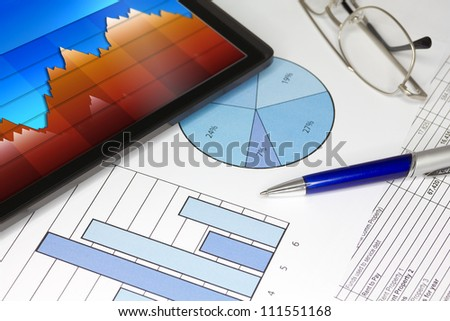 Tablet with Pen Graphs and Spreadsheet of figures - stock photo