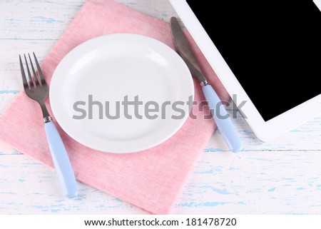 Tablet with plate and cutlery on wooden background - stock photo