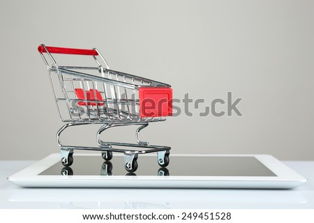Tablet with small shopping cart isolated on white background - stock photo
