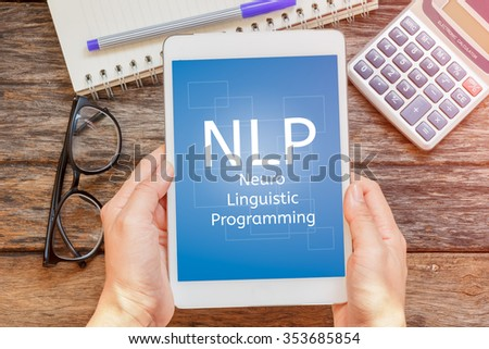Tablet with Text NLP  ( Neuro Linguistic Programming),glasses,notebook and calculator.Business concept. - stock photo