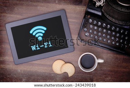 Tablet with Wi-Fi connection on a wooden desk,vintage setting - stock photo
