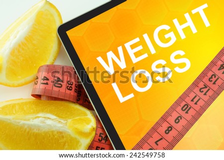 Tablet with words weight loss and measuring tape  - stock photo