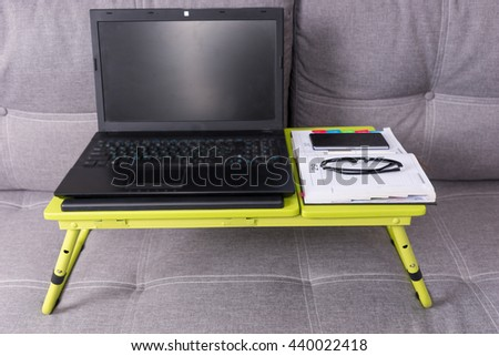 Tabletop workstation on a couch with laptop, stylish eyeglasses, a diary and mobile phone lying on it - stock photo
