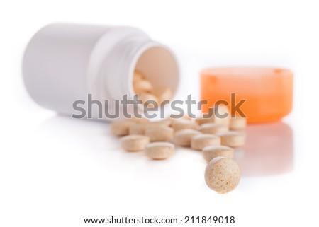 Tablets and a jar on a glossy surface