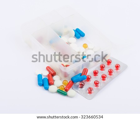 Tablets and capsules in blister packs on white background. - stock photo