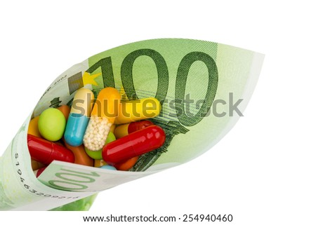 tablets and one hundred euro banknote symbol photo: charges for medicine and drugs the pharmaceutical industry - stock photo
